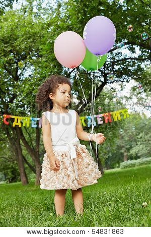 Little girl stands in park, holding three air balloons in her hand, soap bubbles fly around, happy birthday sign behind her back