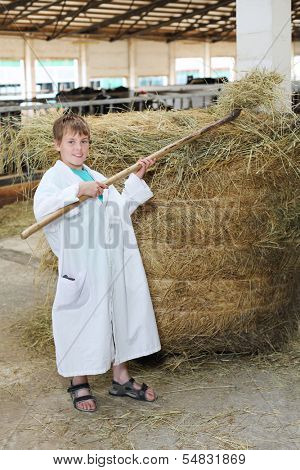 Smiling boy in white coat loads hay by big pitchfork at large cow farm.