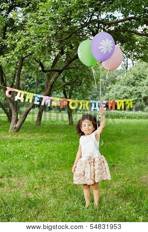 Smiling little girl stands in park, holding three air balloons in her raised hand, happy birthday sign behind her back
