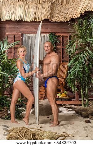 Muscular man in trunks and beautiful girl in swimsuit on a sandy beach with a surfboard