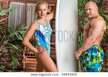 Muscular man and beautiful girl on a beach with a surfboard