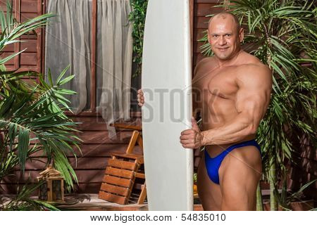 Muscular man in trunks on a beach with a surfboard