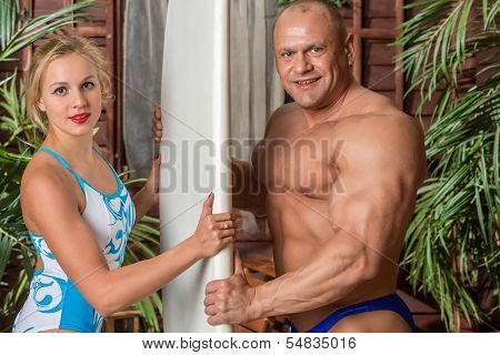Muscular man and beautiful girl in swimsuit with a surfboard near the house with palms