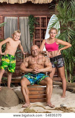 A modern family of three on a sandy beach with a surfboard