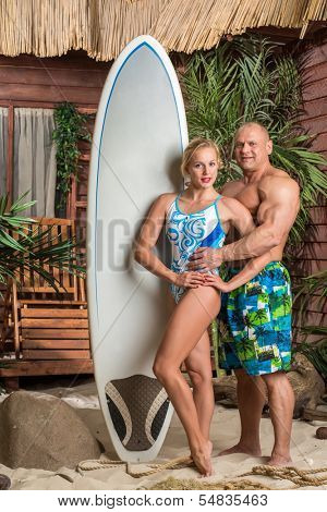 Muscular man and beautiful girl with a surfboard on a beach with palms
