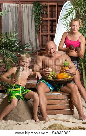 A family of three on a sandy beach with a basket of fruit