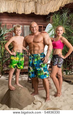 A modern family of three on a sandy beach with a surfboard, son standing on a rock.