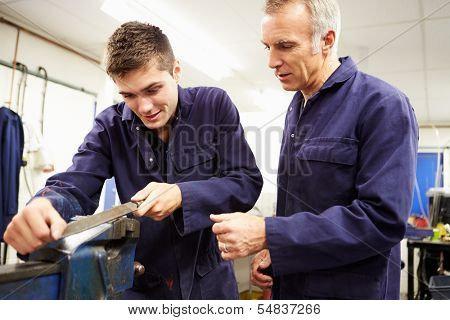 Engineer Checking Trainee's Work On Factory Floor