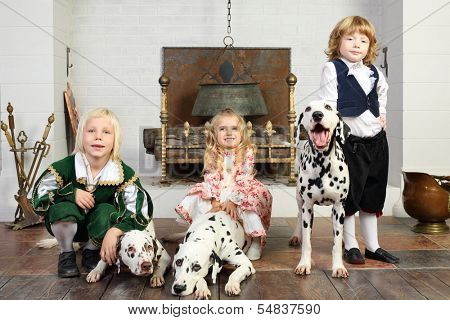Two happy boys and little girl in medieval costumes with three dalmatians sit near fireplace.