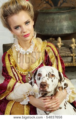 Beautiful woman in red medieval costume sits with dalmatian near fireplace with logs and boiler.
