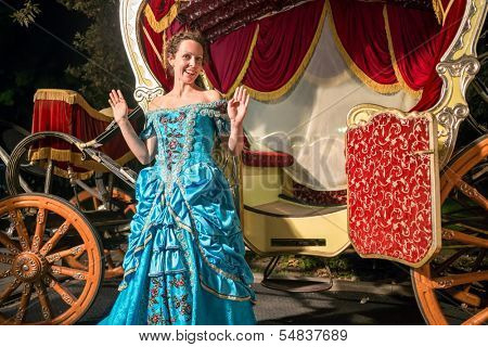The cute girl in blue old-fashioned rised hands up near the carriage