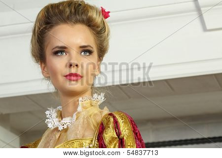 Pretty woman in red medieval costume with flower in hair looks away.