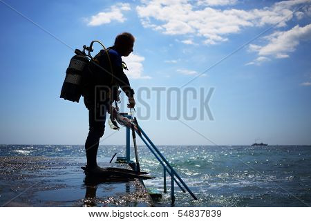 A diver prepares to dive into the water