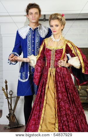 Young man and pretty woman in medieval costumes stand next to fireplace.