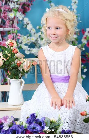 Blonde little girl in white dress sits on bench near bouquet of roses and looks away in room with flowers.