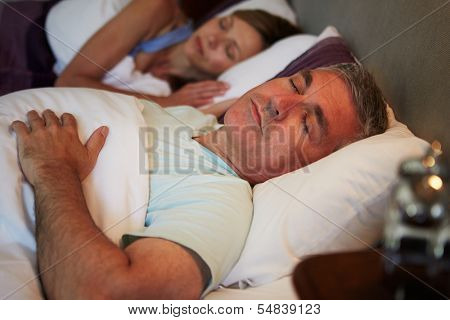 Middle Aged Couple Asleep In Bed Together