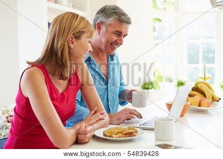 Couple Using Laptop Whilst Having Breakfast In Kitchen