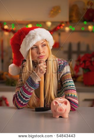 Portrait Of Thoughtful Teenage Girl In Santa Hat With Hammer And Piggy Bank In Christmas Decorated K