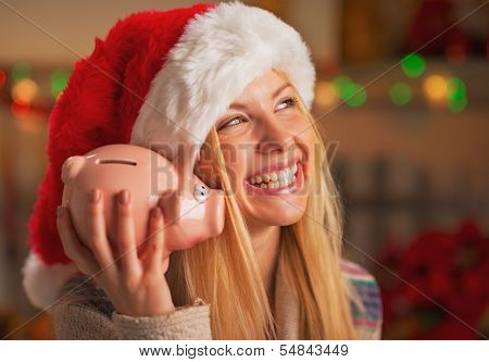 Smiling Teenage Girl In Santa Hat Shaking Piggy Bank