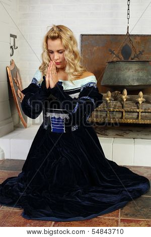 Young woman in medieval costume prays near fireplace with logs.