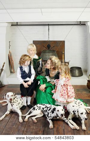 Beautiful woman in medieval costume with three children and three dalmatians scolds boy near fireplace.
