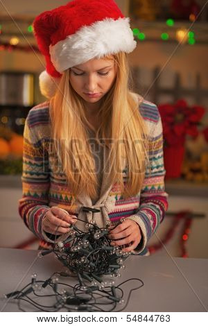 Frustrated Teenage Girl In Santa Hat Untangling Christmas Lights