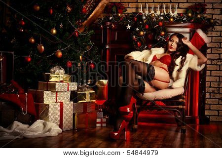 Beautiful young woman in sexual red lingerie and white fur coat posing in Christmas decorations.