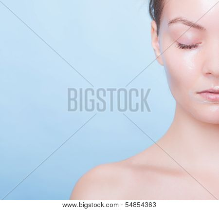 Portrait Blond Girl In Facial Mask On Blue. Part Face. Beauty And Skin Care.
