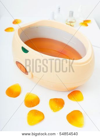 Orange Paraffin Wax In Bowl. Manicure In Beauty Spa Salon.