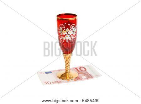 Hermosa copa de vino rojo con tallo oro en billete de diez euros aislado