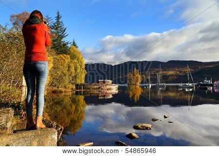 Young woman taking photos at Lochness, Scotland, Europe