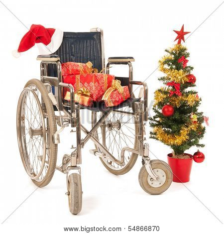 Empty wheelchair with Christmas gifts and tree isolated over white background