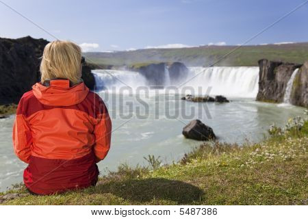 Woman Sitting At Godafoss Waterfall In Iceland