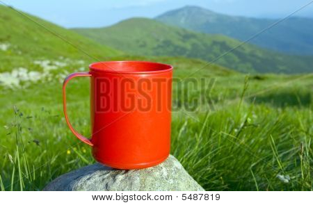Red Cup On Stone In Mountains Camp