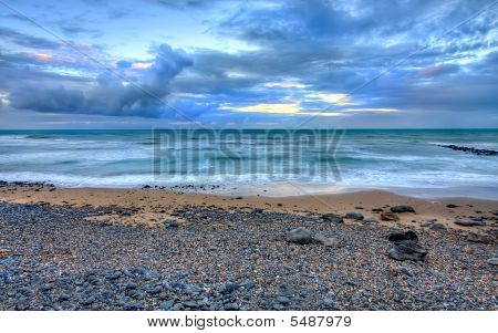 Beach And Dramatic Storm Cloudscape At Dusk