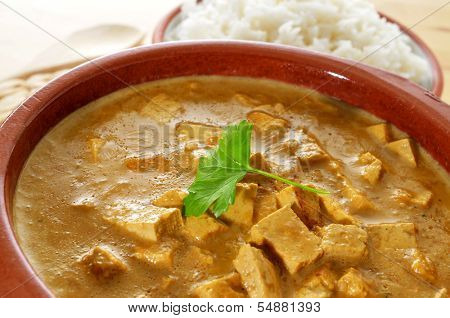 closeup of an earthenware bowl with a coconut and tofu curry served with white rice