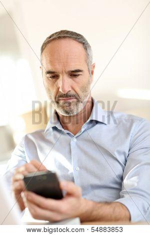 Homem de negócios sênior no escritório usando smartphone