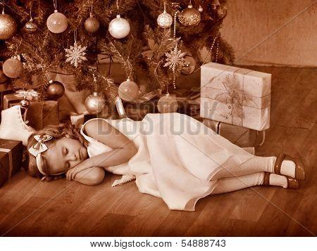 Child sleeping near Christmas tree. Black and white retro.