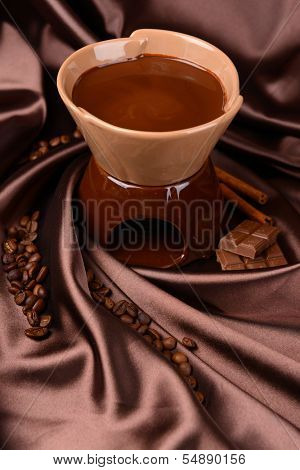Chocolate fondue, on brown background