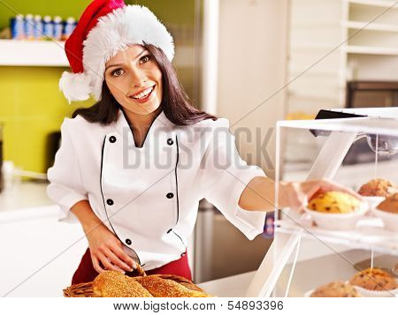 Female chef in Santa hat baking baguette bread.