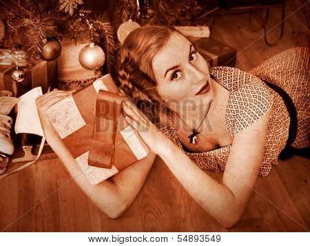 Woman receiving gifts under Christmas tree. Black and white retro.