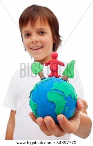 Life in harmony with nature concept - boy holding earth globe with trees and man made of colorful clay