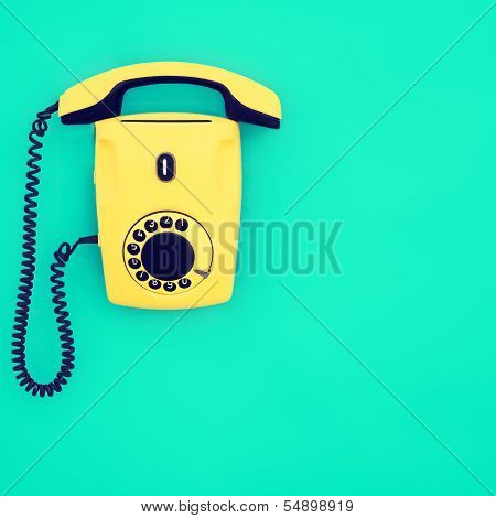 yellow retro telephone on a blue background