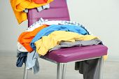 stock photo of sluts  - Heap of  clothes on color chair - JPG