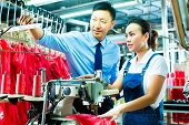 stock photo of labourer  - Seamstress is new assigned to a machine in a textile factory - JPG