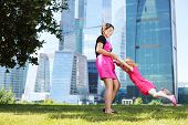 stock photo of bolero  - Beautiful girl circles little girl in red near blue skyscrapers at summer day - JPG