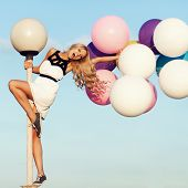 image of hair blowing  - Happy young girl with big colorful latex balloons - JPG