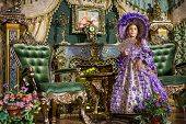 The girl in old-fashioned dress  with fan in beautiful room with gilded furniture