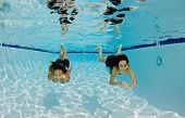 Smiling Girls Swimming Underwater