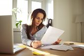 stock photo of contract  - Businesswoman reading a document - JPG